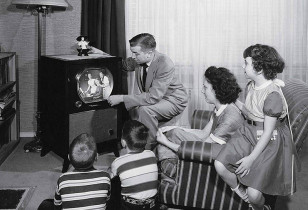parents-with-three-children-watching-television